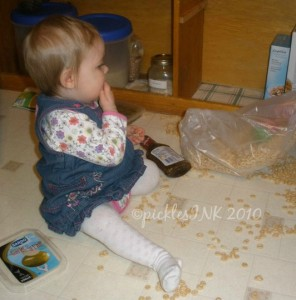Baby Molly eating cereal spilled all over the floor.