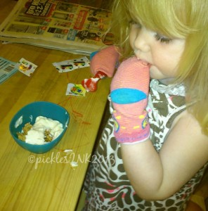 Toddler Molly eating cereal with socks on her hands.