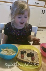 Child making her own snack out of bread, berries, grapes, and cheesy noodles.