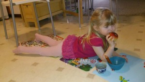 Baby eating apple while lying on placemats on the floor.
