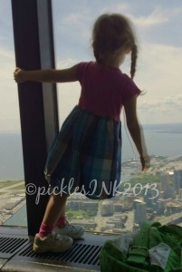 Child standing on the windowsill in the upper observation deck of the CN Tower.