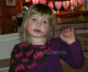Child with face and fingers stained purple from eating frozen blueberries.