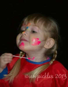 Child smiling and painting her own face.