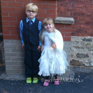Ben and Molly in formal clothing against a brick wall. (Super cute kids formal outfits)