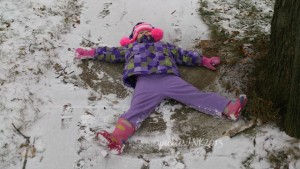 Child making a snow angel in light snow on the sidewalk.