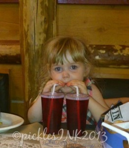 Child drinking from two glasses at the same time.