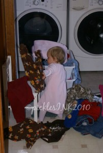 Baby Molly unloading clean laundry from basket.
